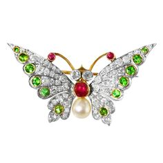 Edwardian Demantoid Pearl Garnet Ruby Diamond Gold Butterfly Brooch. A lovely Edwardian 18 karat gold, platinum, demantoid garnet, diamond, ruby and pearl butterfly brooch, designed as a butterfly with wings extended set throughout with 58 old round-cut diamonds, accented by 12 round demantoid garnets, the body set with 3 round rubies  and a pearl, the pin mechanism is removable and there is a swivel for the pendant loop so the brooch can be worn as a pendant.