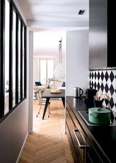 Les architectes Flora de Gastines et Anne Geistdoefer ont imaginé pour cette cuisine noire et blanche une verrière façon atelier afin de profiter de la lumière naturelle qui provient de l'entrée.