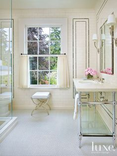In the master bath, an Aquatic tub sits beneath a vaulted ceiling with a Vaughan alabaster-and-bronze light fixture. The floors include a custom marble mosaic..
