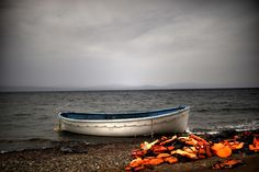Life jackets and a boat that were used by refugees and migrants to cross the Aegean Sea from Turkey lie abandoned on a beach on the Greek Island of Lesbos