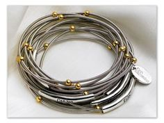 twelve bracelets made from piano wire, accented with tiny gold beads