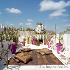 MOROCCO  The roof top terrace features an outdoor fireplace and is punctuated by painted plant pots with a leather rug and scatter cushions upholstered in Kuba cloth