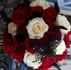 bridal bouquet with red and white roses with jewels, black feathers, and black butterfly