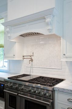 Gorgeous kitchen features a white curved range hood adorned with French corbels situated over a swing-arm pot filler mounted on a white mosaic stove backsplash and a stainless steel stove with an under the counter microwave to the left. Stove Backsplash, White Kitchen Backsplash, Kitchen Hoods, Kitchen Stove, Kitchen Redo, Kitchen Tiles, Home Decor Kitchen, Kitchen Interior, New Kitchen