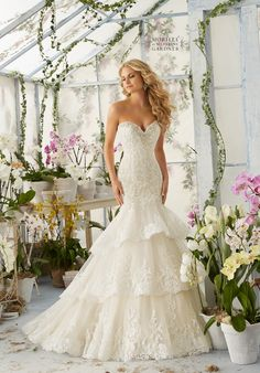 CRYSTAL MOONSTONE BEADING MEETS ALENCON LACE APPLIQUES AND SCALLOPED EDGING ONTO THE TIERED TULLE GOWN