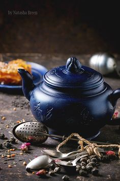 Blue ceramic teapot and plate with honeycombs, served with spoons, black and green tea lives over dark background