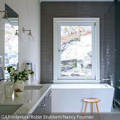 Die graue Backsteinwand sorgt für einen Hauch von Industrie-Chic in diesem Badezimmer. Die eckige Badewanne nutzt das schmale Bad optimal aus.
