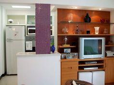 Neste espaço, de 40 m², a sala de estar, a sala de TV e a cozinha foram integradas pela designer de interiores Ana Lucia Nunes Gomes. Ao demolir a parede que separava a sala da cozinha, apareceu uma coluna, que acabou servindo de destaque para a integração dos ambientes.