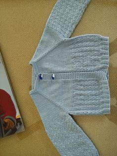 De algodón, canesú a punto de jersey y caladito sencillo en el resto. Chaquetita empezada por el cuello.