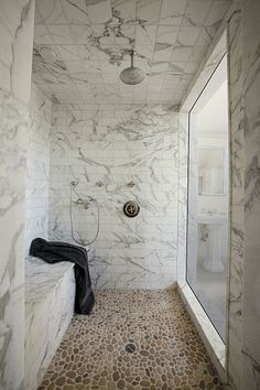 Stone everywhere in this marble shower with a pebble mosaic floor. Gorgeous and simple.
