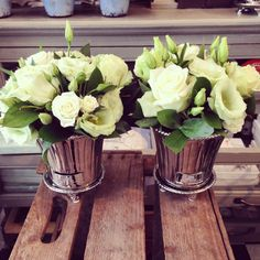 Pretty white and green party table arrangements in our new Lene Bjerre pots. https://www.theonlinesecretgarden.com/product/lene-bjerre-silver-round-flower-pot-with-stand/