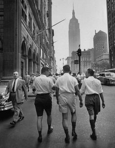 Three young businessmen wearing Bermuda shorts on Fifth Ave. during lunchtime. Photograph by Lisa Larsen. New York City, 1953.