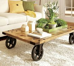 muebles con palets, mesa de madera reciclada con ruedas de metal, sofa con cojines, alfombra y flores