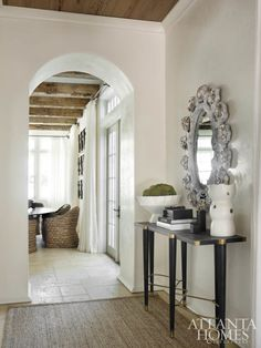 An artful oystershell mirror and a handsome console from Gabby hold court in the foyer.