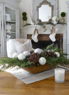 Dough bowl with white and silver ornaments, large pine cones and greenery, and french ticking cloth liner.