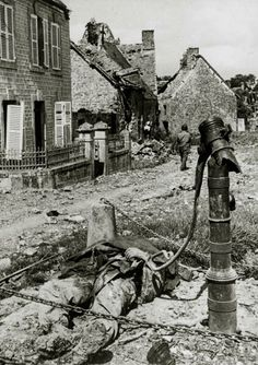War and Conflict, World War Two, (D-Day), Invasion of France, pic: June 1944, The scene at the village water pump in Ste, Marcouf, Normandy, shows a dead American soldier, who when trying to quench his thirst, had set off a German made booby trap (Photo by Popperfoto/Getty Images)