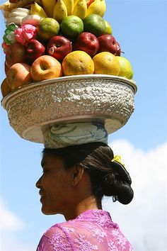 Woman carrying a basket full of fruits, Bali, Indonesia by Eric Lafforgue