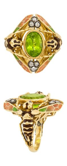 An Art Nouveau gold, silver, plique-à-Jour enamel, peridot and diamond Double Wasp ring, France, circa 1900. The 18k yellow gold ring set to the centre with an oval peridot weighing 5.00 carats, and further set with European and single-cut diamonds, with French assay mark.