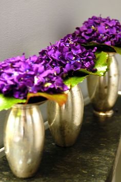 Budget centerpiece ideas: Bright purple sweet peas clustered in small silver vases add a flash of color.