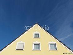 Fenster im gelben Dreieck einer Fassade vor blauem Himmel in Markt Burgheim in Oberbayern