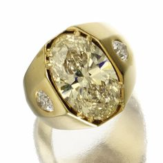 DIAMOND RING The oval diamond weighing 8.88 carats, flanked by 2 pear-shaped diamonds weighing approximately .90 carat, set within an 18 karat gold tapering band.