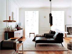 Minimalist living room, black leather lounge, wood console, white walls, black metal pendant lights