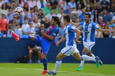Andres Iniesta (L) of FC Barcelona strikes the ball during the La Liga match between Deportivo Leganes and FC Barcelona at Estadio Municipal de Butarque on September 17, 2016 in Leganes, Spain.