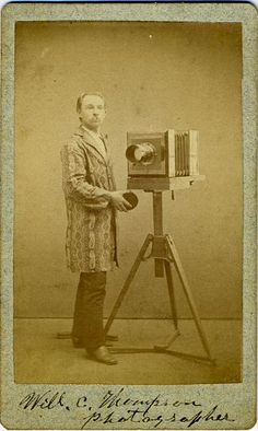 """PHOTOGRAPHER WITH CAMERA. Carte de visite;,  4 1/4"""" x 2 1/2"""". Autographed photo of Will C. Thompson, photographer holding the lens cap."""