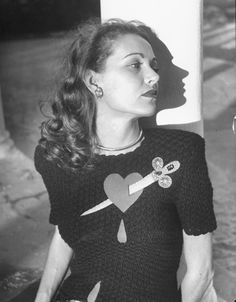 Broken heart? Nina Leen photographs a model wearing a sweater with a heart pierced by jeweled dagger. See more of Leen's work here. (N...