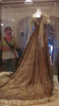 Silken peacock dress.  Dress was worn by Lady Mary Curzon (Vicereine of India) to the coronation of King Edward VII (of Britian) in 1902. Dress is covered in peacock feathers, beetle wings, and gold and silver beadwork and weighs over 10 lbs.