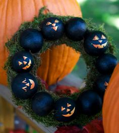 Add jack-o'-lantern faces to a cute wreath for your Halloween-theme door. Paint about a dozen floral pods with black acrylic paint. Adhere stickers or use a liner brush to paint cheerful (or scary) faces on several of the pods. Once dry, use double-stick tape or a T-pin to adhere to a floral wreath. Settle the wreath in between pumpkins or hang with a thick silk ribbon./
