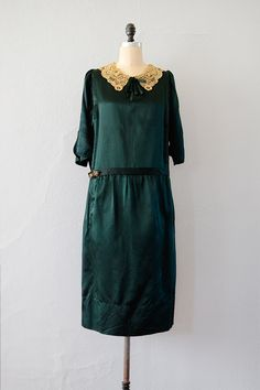 1920s hunter green silk drop waist dress is straight cut throughout with matching sash (which we have used a brooch to close, but this is sold separately). Cream colored lace collar was probably added after the dress was made and is centered with a bow. Sleeves have slit detail.
