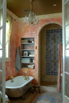 New Orleans Elegance With Patterned Blue And White Shower Tiles Coral Walls Crystal Chandelier And A Clawfoot Bathtub