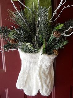 Festive door decor. Mittens stuffed with pine boughs, white painted twigs, and glittery pinecones. Great way to use unworn mittens.
