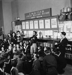 """""""Activist folk musician Woody Guthrie playing for a crowd that includes servicemen at a New York USO club during WWII."""" 