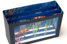 """""""The construction of this aquarium card is basically the same as with the familiar Card In A Box style card. Only difference is that I added the struts on both the top and bottom of the box and cut a window in the front panel. The paper pieced fish were glued onto strips of clear acetate which were attached to the top and bottom struts, to make them appear to be swimming in the aquarium. Coral and seaweed were attached"""""""