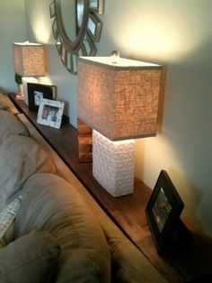 Love this... create a fake sofa table by building a shelf behind your sofa. Great for small living rooms if you need space to add lamps / decor