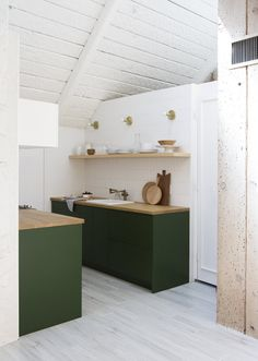 A Chic, Renovated A-Frame in Palm Springs Asks $535K - Photo 4 of 13 - Here is a view into the kitchen, which received IKEA cabinet boxes with Semihandmade drawer and door fronts painted Chard from Behr, by Samuel. The refrigerator is a KitchenAid model tucked under the butcher block counter and covered with a panel.