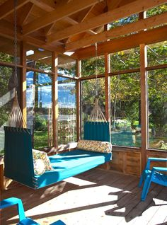 Glass enclosed porch with blue hammock daybed and colorful bolster pillows next to coordinating blue patio furniture. Beyond cute sunroom design!