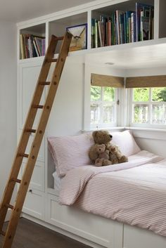 Clever bedroom idea. Lots of storage surrounding the bed, which is nestled snugly in a nook with a window. Great library ladder to reach the higher storage cubbies.!
