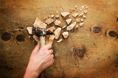 Hand with hammer breaks a stone by WonderMe on Creative Market