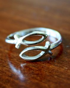 This symbolic sterling silver fish ring can be worn everyday to symbolize your Christian Faith. The adjustable band of the ring is the outline of a Christian fish, which is a traditional symbol for Christ and Christians, also known as Ichthys. Shop our complete line of Christian Ichthus jewelry, which includes an Ichthus Pair of Earrings, Bracelet and Pendant for a Necklace.