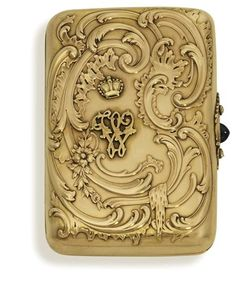 A jewelled gold cigarette-case  marked Fabergé, workmaster's mark of Michael Perchin, St. Petersburg, circa 1890 Rectangular with rounded angles, the cover repouseé, chased and engraved with rocaille and floral scrolls, the base with similar decoration to one corner, with cabochon sapphire push-piece flanked by diamond-set scrolls, with later applied crowned initial W, marked inside cover and base.