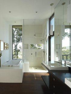 Glänzend mit Tageslicht aus Klarglas Windows, ist das weiß an den Wänden, Duschboden und Decke, ordentlich und hell. Der dunkle Holz Boden und Eitelkeit Zähler kontrastieren schön und stellen eine große Bereicherung für das Badezimmer ästhetische.