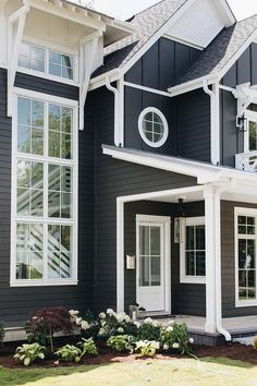Navy blue home with white trim displaying glass windows and a lush front porch garden. Navy House Exterior, White Exterior Houses, Craftsman Exterior, Exterior Paint Colors For House, Exterior Design, Exterior Colors, Siding Colors, Exterior Siding, Dark Blue Houses