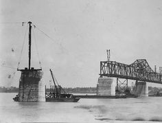 """Side view from Louisville, Kentucky, shore (at left) of Municipal Bridge under construction in 1929; supports and wires await the next span. The bridge links Louisville, Kentucky, to Jeffersonville, Indiana. On back of image: """"New York Studio Anything Photographic Louisville, Ky."""" Now known as the George Rogers Clark Memorial Bridge or the Second Street Bridge, it spans the Ohio River between Kentucky and Indiana. The bridge was placed on the National Register of Historic Places in 1984."""
