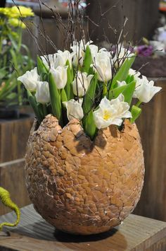 Paper mache over large balloon, covered in egg shells. Pop & add a vase for water or potted plant.   IDEA