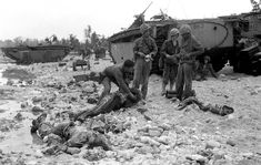 U.S. Marines of the first Marine Division stand by the corpses of two of their comrades, who were killed by Japanese soldiers on a beach on Peleliu island, Republic of Palau, Sep. 14, 1944