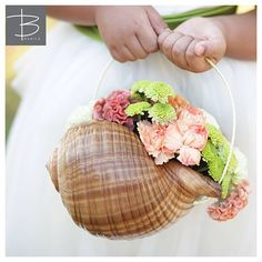 Bespokemanila: Flower girls carried orange and green blooms placed in a shell for that perfect Boracay vibe.    Photo by Mimi and Karl  Bouquet by April and Karen Yu