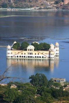"""The Sunken Palace, Udaipur, India. The """"Lake Palace"""" is a luxury hotel, of 83 rooms and suites featuring white marble walls, located on a natural foundation of 4 acres (16,000 m2)rock on the Jag Niwas Island in Lake Pichola, Udaipur, India. The hotel operates a speed boat which transports guests to the hotel from a jetty at the City Palace. It has been voted as the most romantic hotel in India and in the world."""